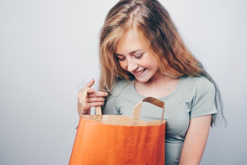 Belle fille caucasienne blonde souriant et regardant dans un sac à provisions photos stock