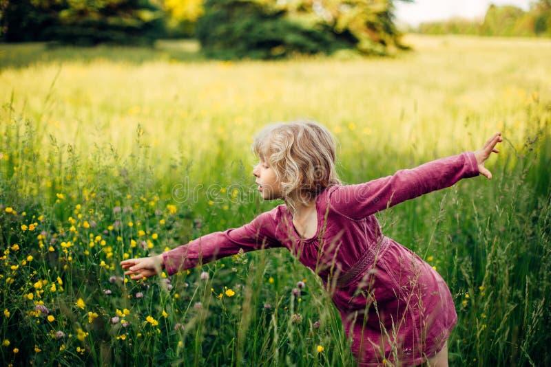 Belle fille caucasienne dans une grande herbe à l'ombre au coucher du soleil image libre de droits