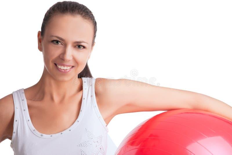 Belle fille caucasienne de sourire avec le fitball rouge photo libre de droits
