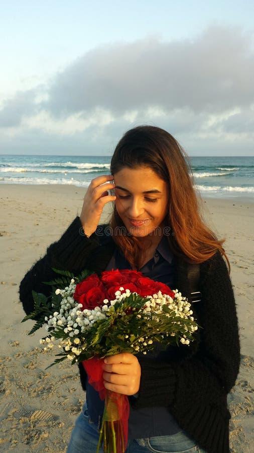 Belle fille caucasienne regardant un bouquet des roses rouges le Th images libres de droits