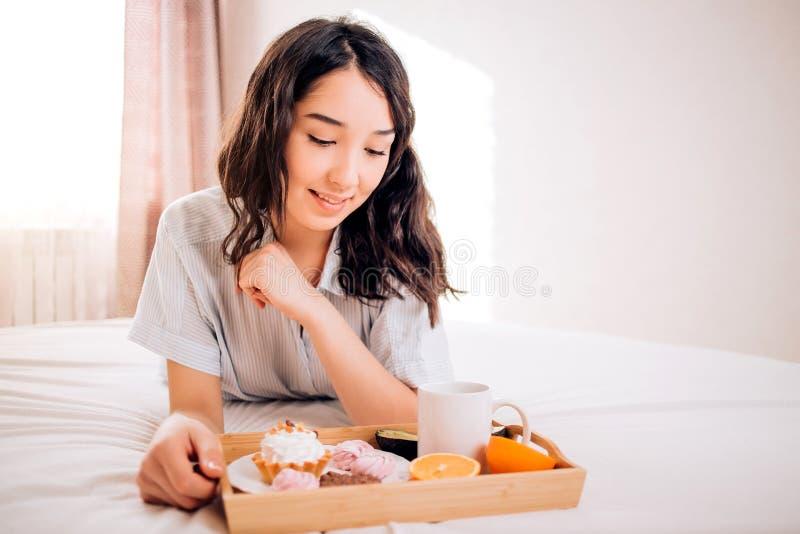 Belle fille caucasienne tendre dans des pyjamas souriant regardant la détente loin de repos à la maison Apprécier joyeux stupéfia photos stock