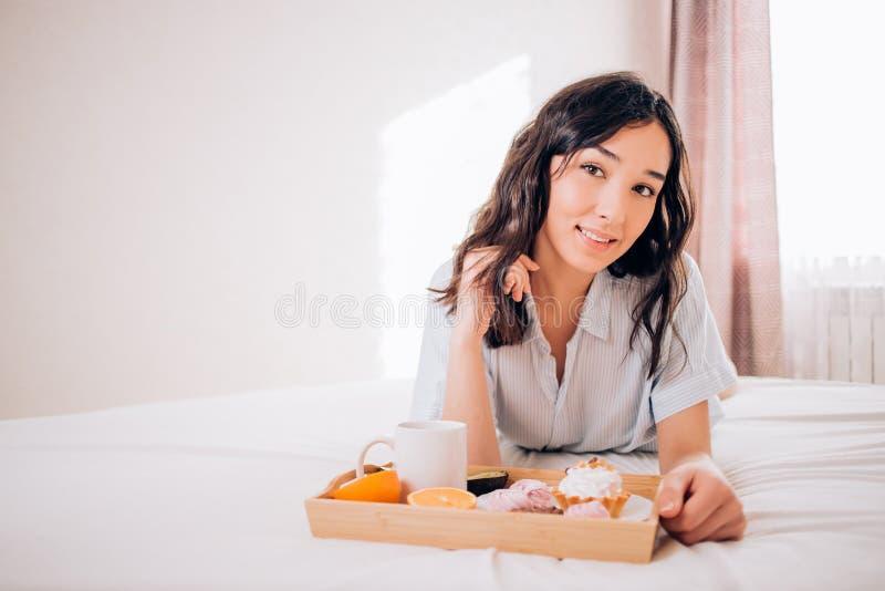Belle fille caucasienne tendre dans des pyjamas souriant regardant la d?tente loin de repos ? la maison Appr?cier joyeux stup?fia images stock