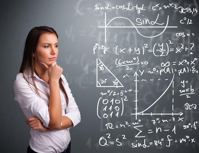 Belle fille d'école pensant aux signes mathématiques complexes photo libre de droits