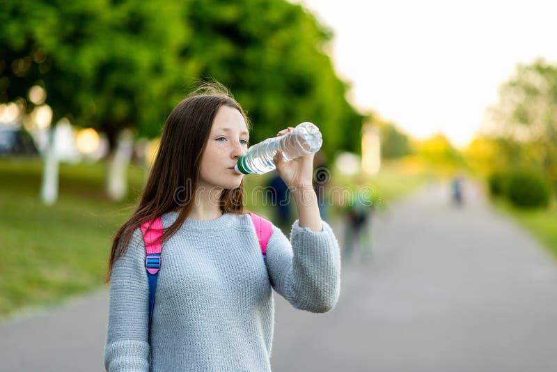 Belle fille d'écolière Nature d'été Il tient une bouteille de l'eau et boit Brunette avec le long cheveu Derrière photo stock
