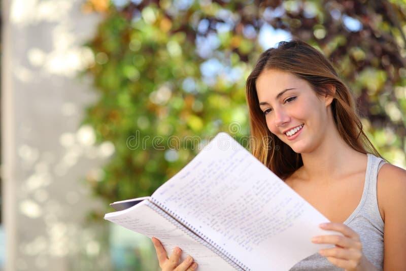 Belle fille d'adolescent étudiant lisant un carnet extérieur photographie stock