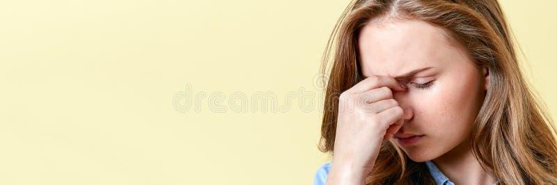 Belle fille d'adolescent avec des cheveux et des taches de rousseur de gingembre ayant le mal de tête et les yeux endoloris Étudi image stock