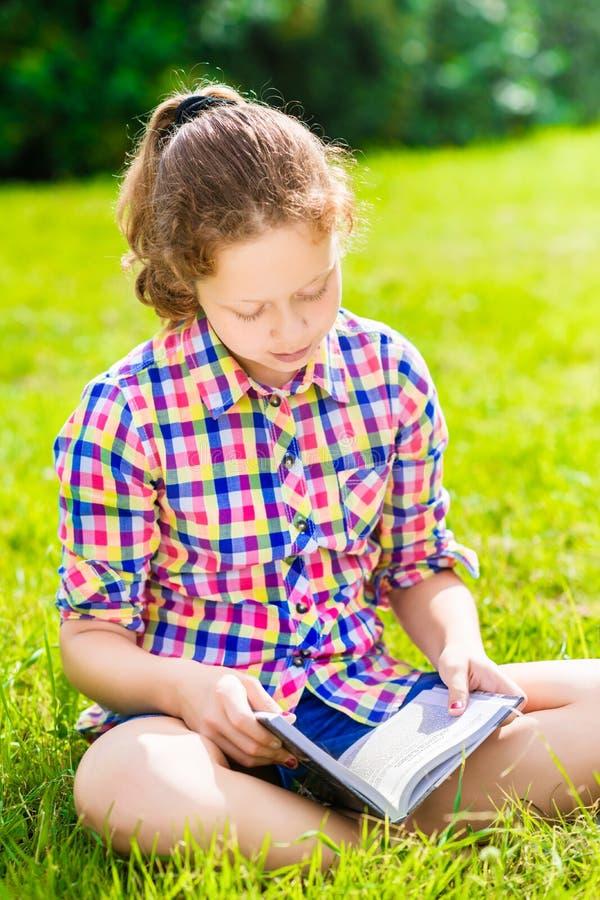 Belle fille d'adolescent s'asseyant sur l'herbe et le livre de lecture photographie stock