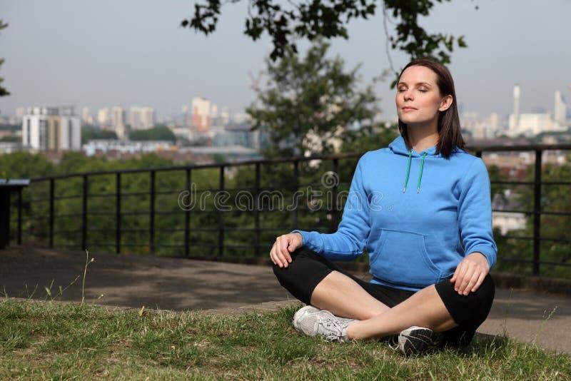 Belle fille d'ajustement méditant en soleil chaud photo libre de droits
