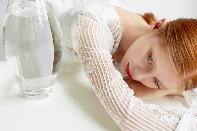 Belle fille d'aspect européen Cheveux rouges avec d'un petit peu du miel Tir de beauté Un récipient de l'eau Un symbole de photo libre de droits