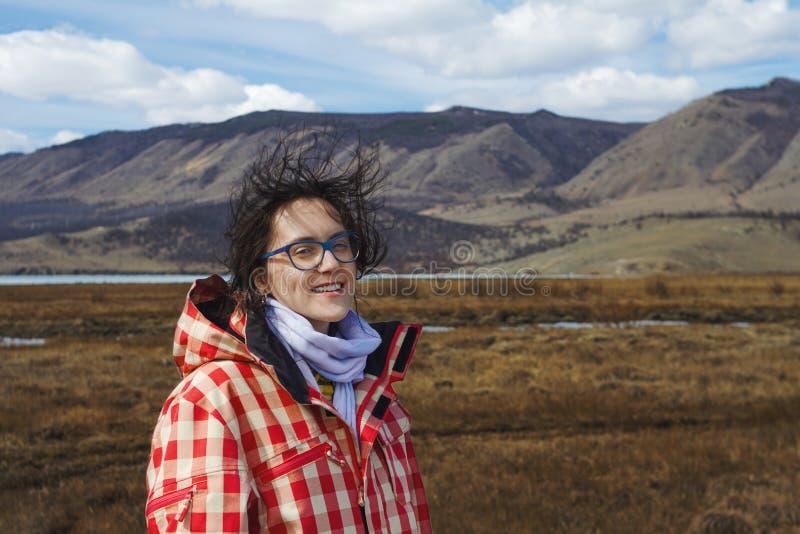Belle fille d'aspect européen dans les montagnes scéniques sur le lac Baïkal au printemps sur le champ pendant un vent violent et image stock