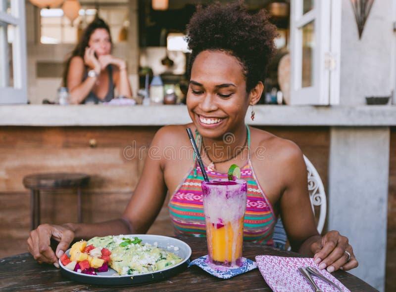 Belle fille d'habitant des îles du Pacifique de métis en café végétarien pour le petit déjeuner avec l'enveloppe et la salade et  photographie stock libre de droits