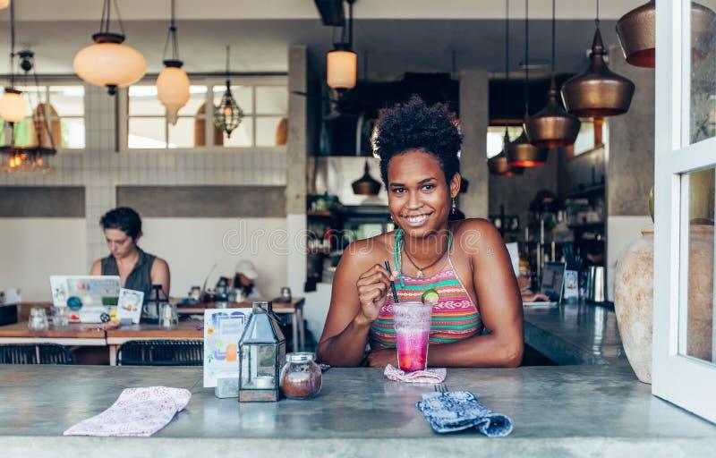 Belle fille d'habitant des îles du Pacifique de métis en café végétarien pour le petit déjeuner avec le smoothie frais de mélange photos libres de droits