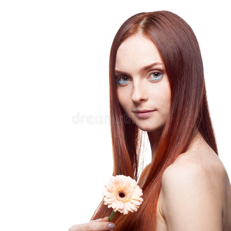 Belle fille d'une chevelure rouge retenant la fleur images stock