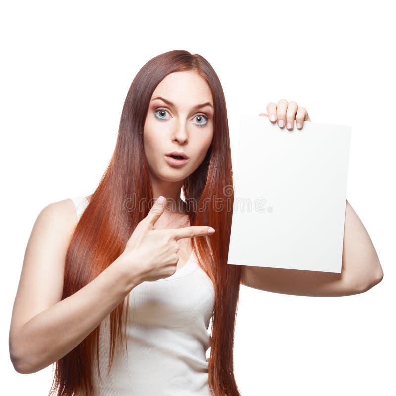 Belle fille d'une chevelure rouge retenant le signe images stock