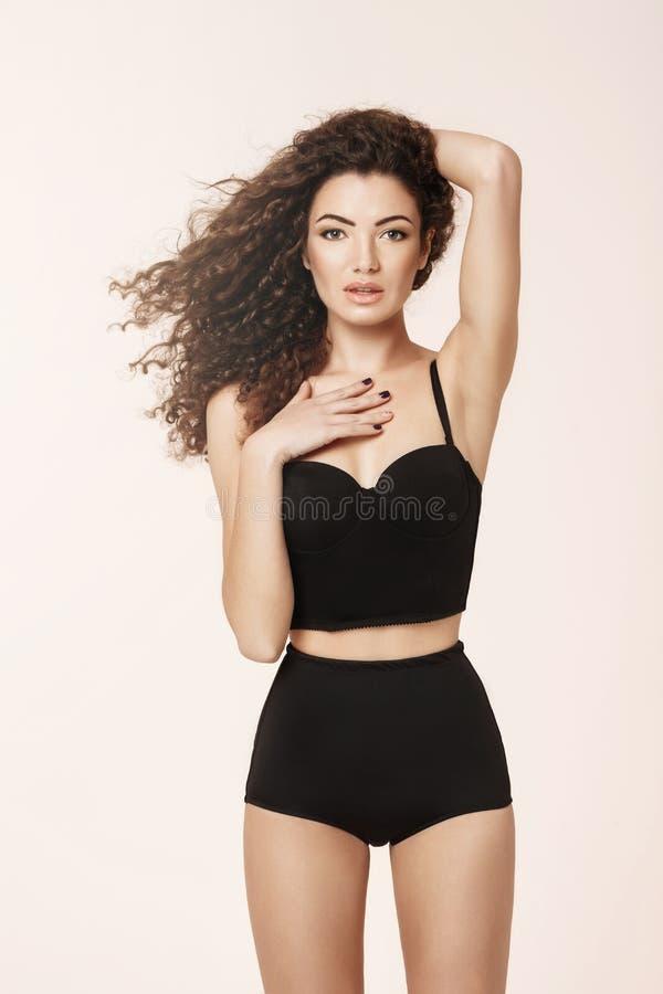 Belle fille dans de rétros sous-vêtements noirs regardant l'appareil-photo posant au-dessus du fond rose images libres de droits