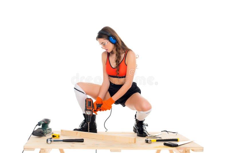 belle fille dans des écouteurs protecteurs fonctionnant avec le foret électrique à la table en bois avec des outils, images stock