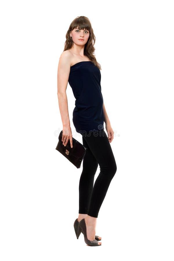 Belle fille dans des guêtres noires avec un sac à main images stock