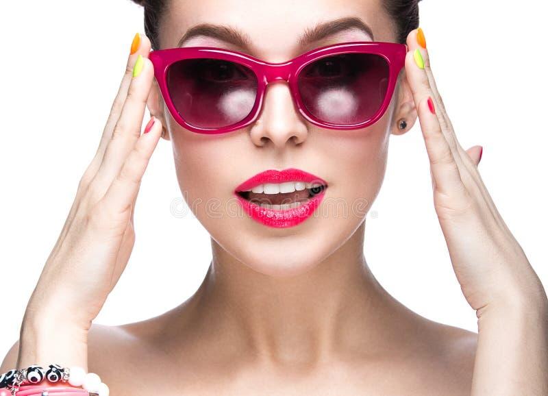Belle fille dans des lunettes de soleil rouges avec le maquillage lumineux et les clous colorés Visage de beauté photo libre de droits