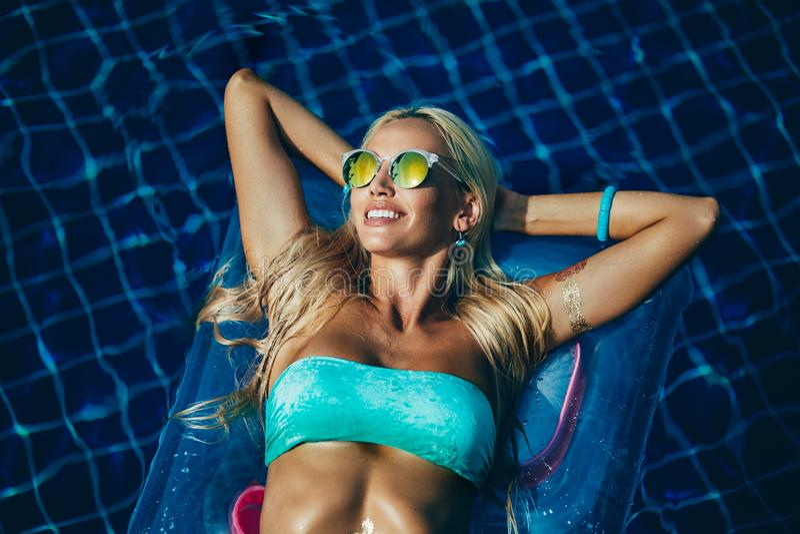 Belle fille dans des lunettes de soleil se trouvant sur une eau, une détente et un havi image stock