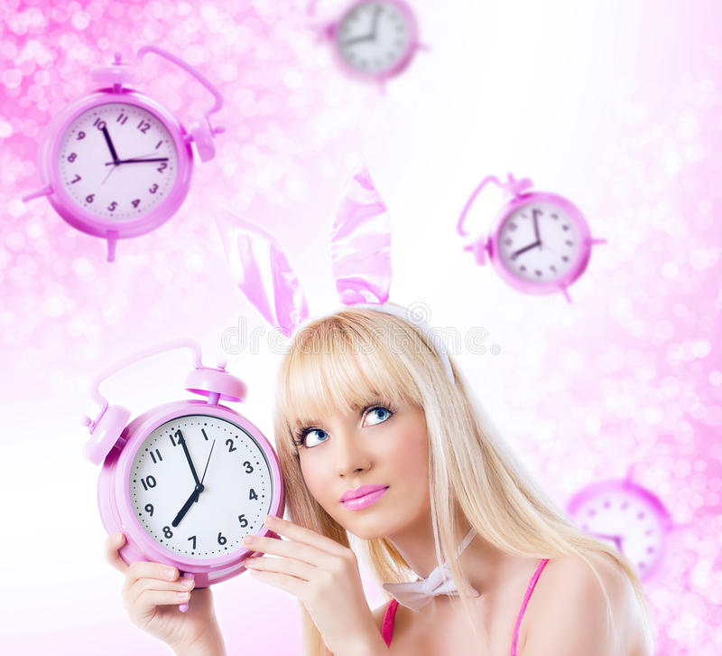 Belle fille dans des oreilles de lapin retenant l'horloge image libre de droits