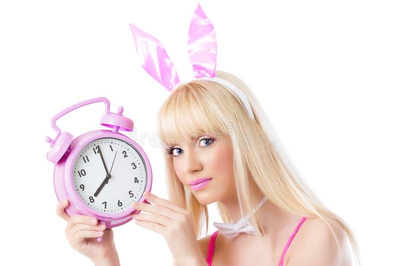 Belle fille dans des oreilles de lapin retenant l'horloge rose images stock