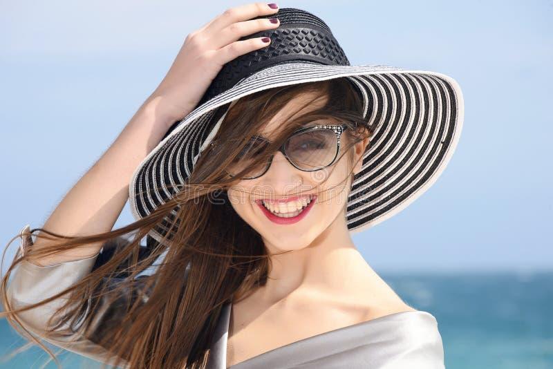 Belle fille dans l'équipement de mode souriant par la mer images libres de droits