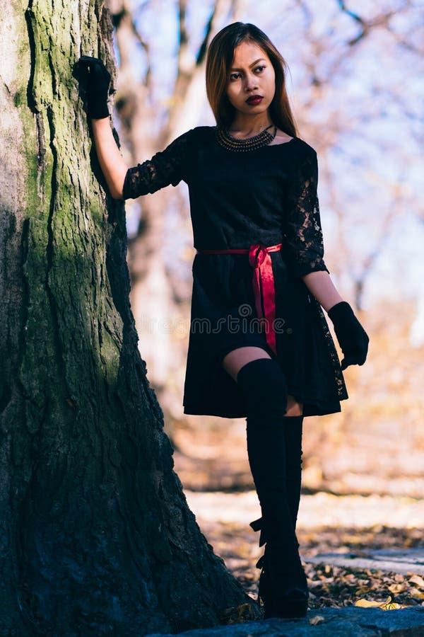 Belle fille dans l'équipement noir avec des gants et de longues chaussettes, posant photos stock