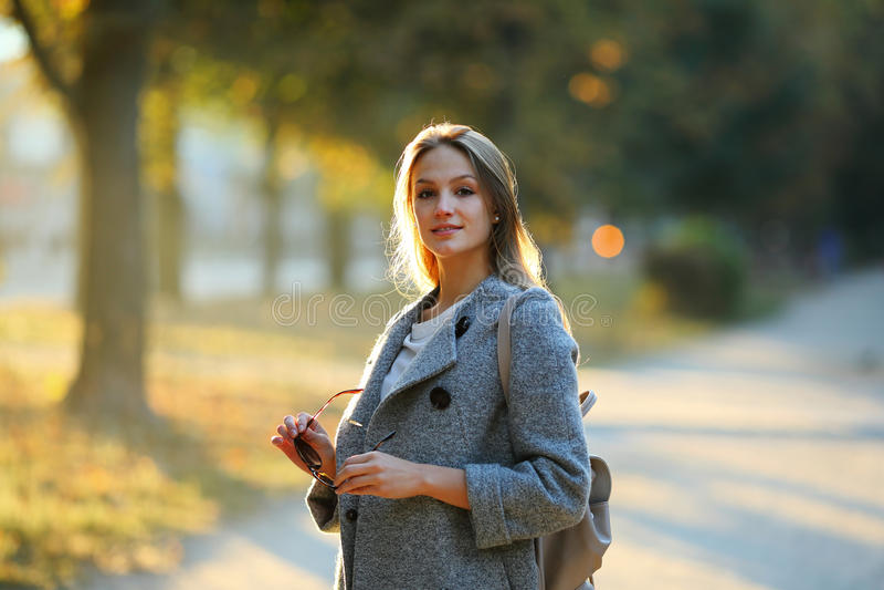 Belle fille dans l'allée de parc tenant des sunlasses photographie stock