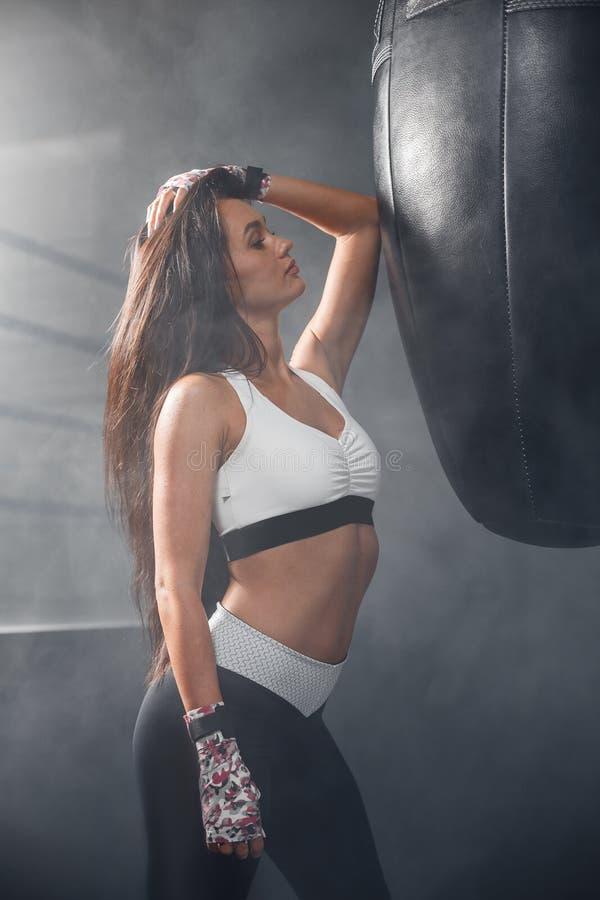 Belle fille dans l'uniforme de sports posant près d'un sac de sable dans le gymnase photos stock