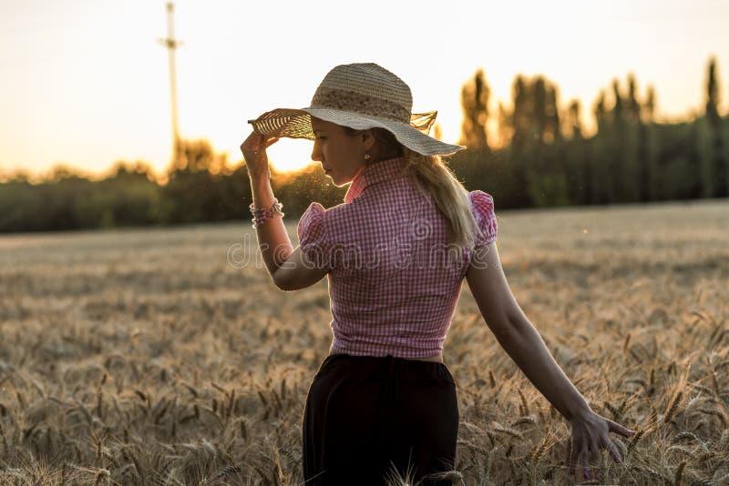 Belle fille dans la marche par le champ de blé images stock