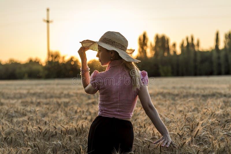 Belle fille dans la marche par le champ de blé photographie stock libre de droits
