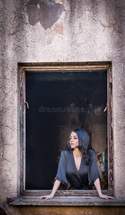 Belle fille dans la pose noire dans un vieux châssis de fenêtre Longue brune attrayante de cheveux rêvassant dans le bâtiment de  photo stock