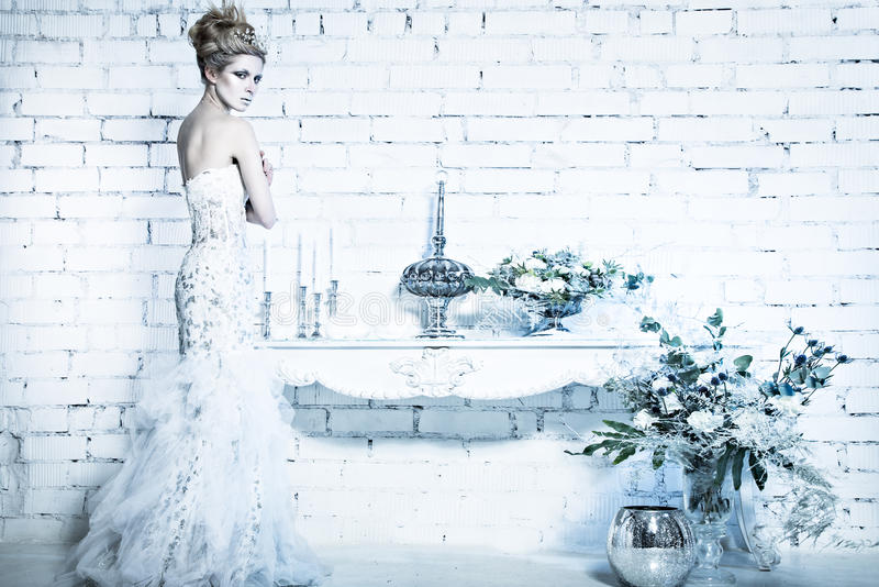 Belle fille dans la robe blanche dans l'image de la reine de neige avec une couronne sur sa tête image stock