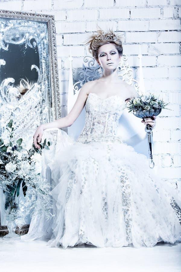 Belle fille dans la robe blanche dans l'image de la reine de neige avec une couronne sur sa tête photo libre de droits