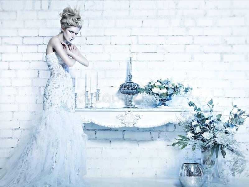 Belle fille dans la robe blanche dans l'image de la reine de neige avec une couronne sur sa tête photographie stock