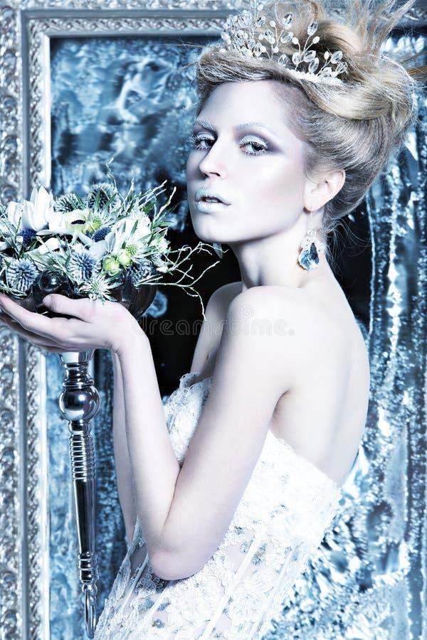 Belle fille dans la robe blanche dans l'image de la reine de neige avec une couronne sur sa tête photos libres de droits