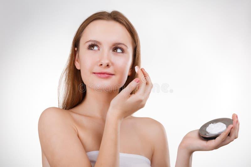 Belle fille dans la salle de bains et masque pour des soins de la peau faciaux image stock