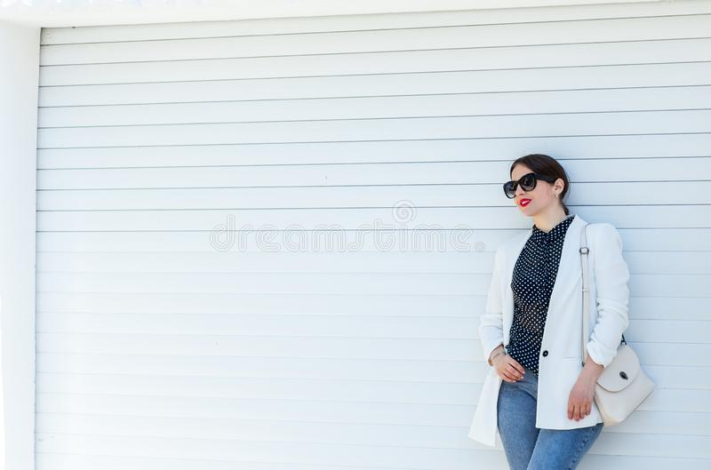 Belle fille dans la veste et des jeans blancs au fond blanc de mur de porte de garage Été occasionnel à la mode d'équipement de m images stock