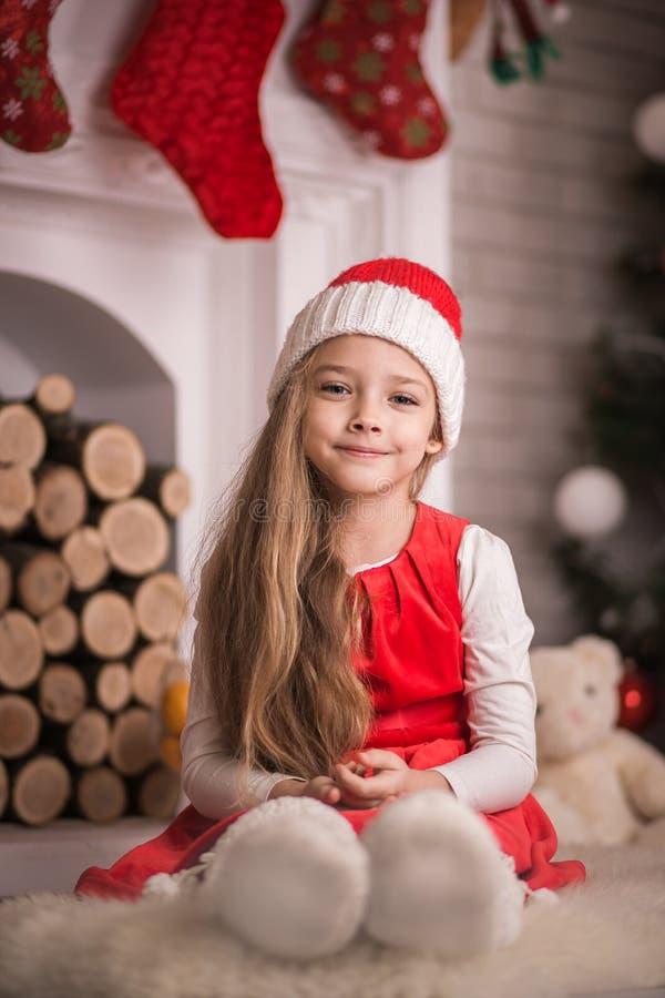 Belle fille dans le chapeau de Santa se trouvant sur le plancher, tir de studio, modifiant la tonalité dans le style de vintage photo stock