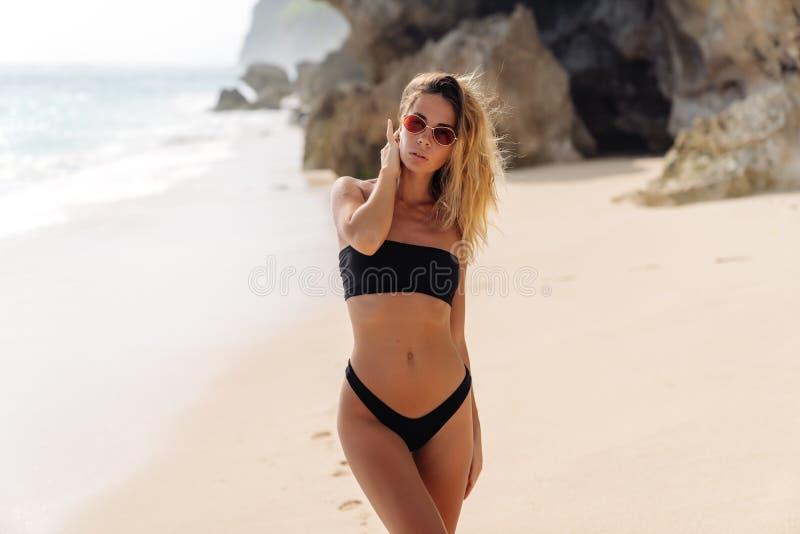 Belle fille dans le maillot de bain noir et des lunettes de soleil se reposant près de l'océan sur la plage photos libres de droits