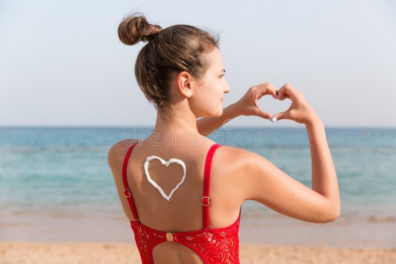 Belle fille dans le maillot de bain rouge avec la protection solaire dans la forme du coeur au fond à la plage photo libre de droits