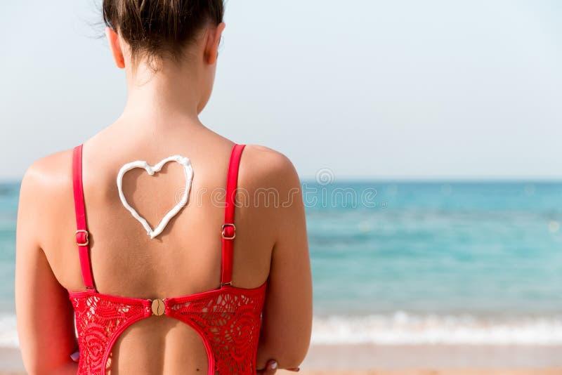Belle fille dans le maillot de bain rouge avec la protection solaire dans la forme du coeur au fond ? la plage image stock