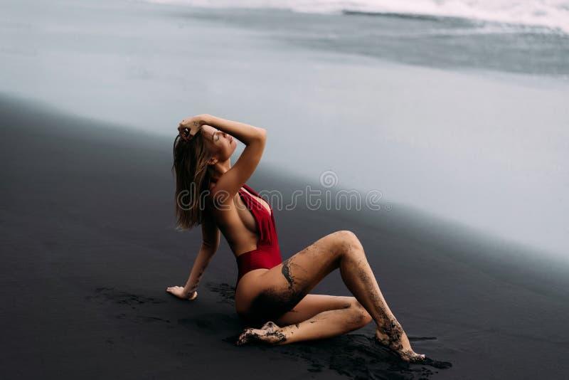 Belle fille dans le maillot de bain rouge se trouvant sur la plage avec le sable volcanique noir photos libres de droits