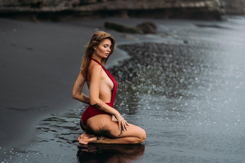 Belle fille dans le maillot de bain rouge se trouvant sur la plage avec le sable volcanique noir images libres de droits