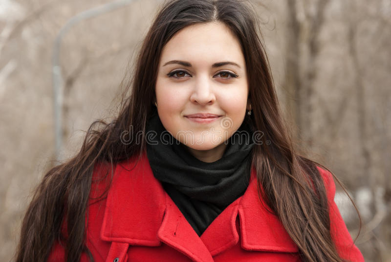Belle fille dans le manteau rouge et son sourire image libre de droits