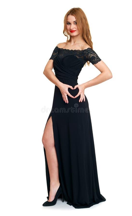 Belle fille dans le symbole noir de coeur d'exposition de robe de la main, d'isolement sur le fond blanc, les vacances de valenti photos libres de droits