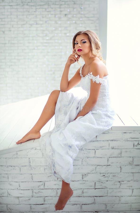 Belle fille dans les rêves blancs d'une robe de se reposer sur le mur photographie stock libre de droits