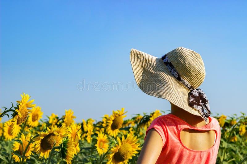 Belle fille dans un chapeau parmi un tournesol photographie stock libre de droits
