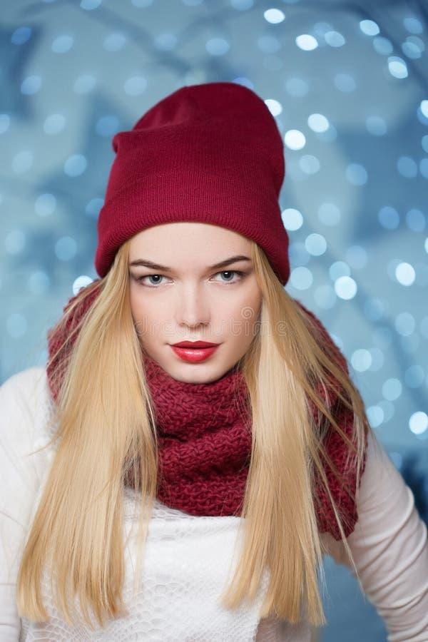 Belle fille dans un chapeau rouge à une guirlande de Noël image stock