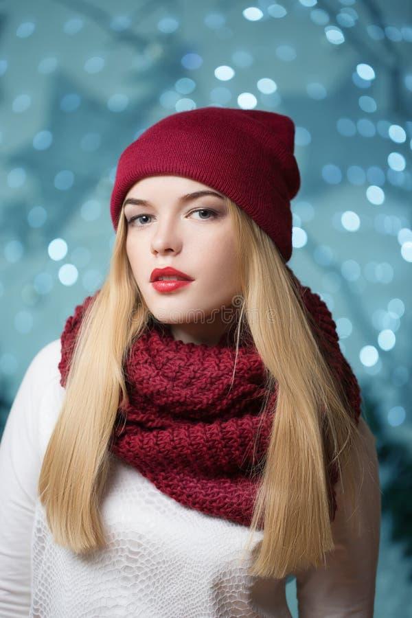 Belle fille dans un chapeau rouge à une guirlande de Noël images stock